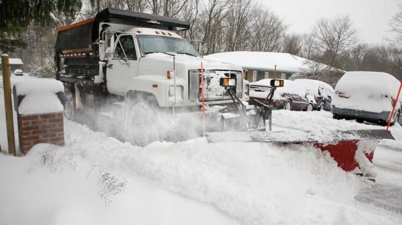 snow plows in snow storm